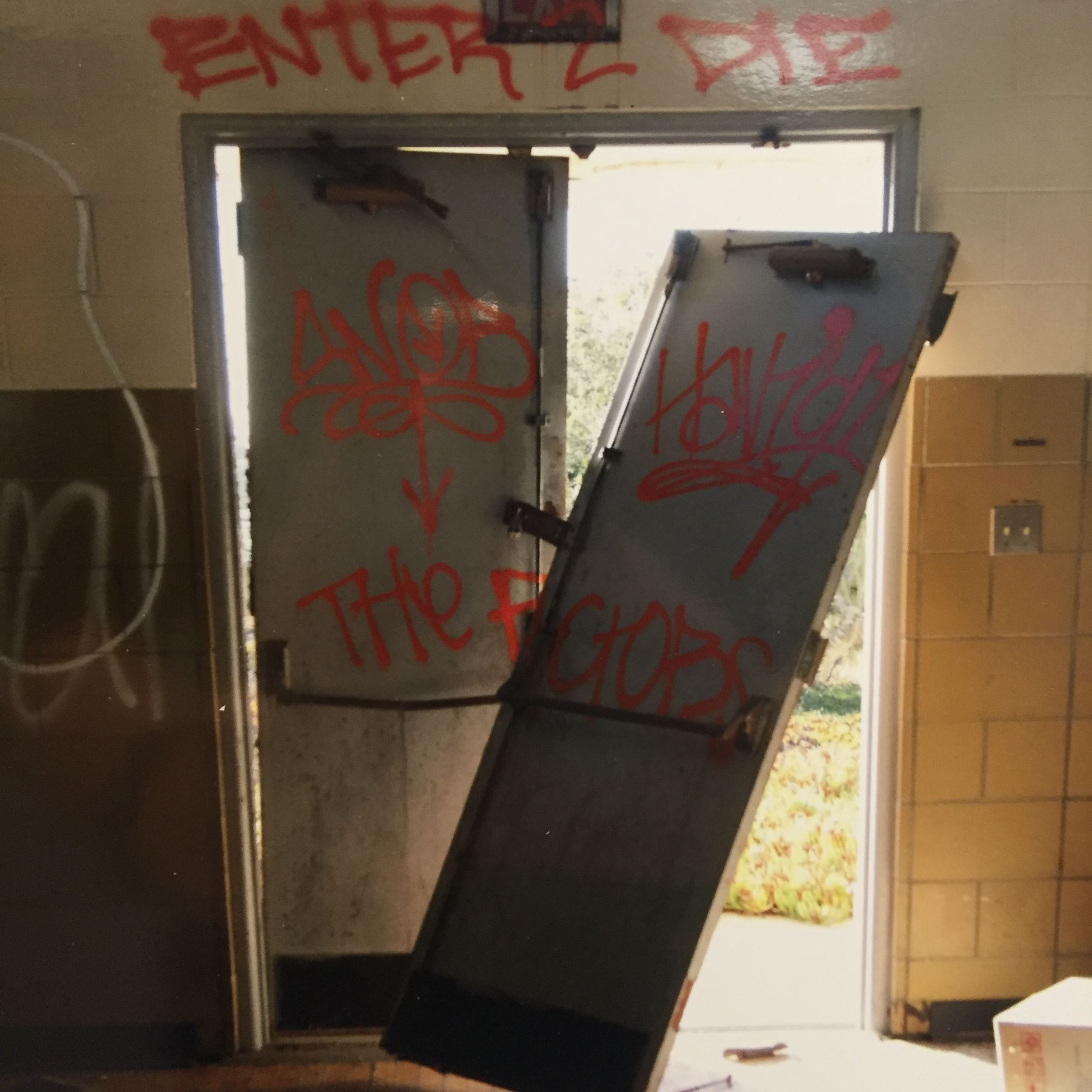 Photograph of graffiti on door with one door off the hinges