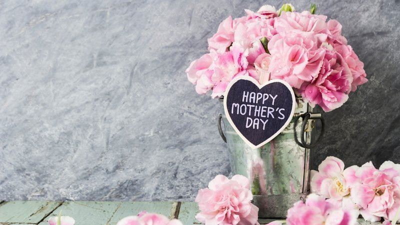 "Pink flowers in vase with hard sign that says ""Happy Mother's Day"""