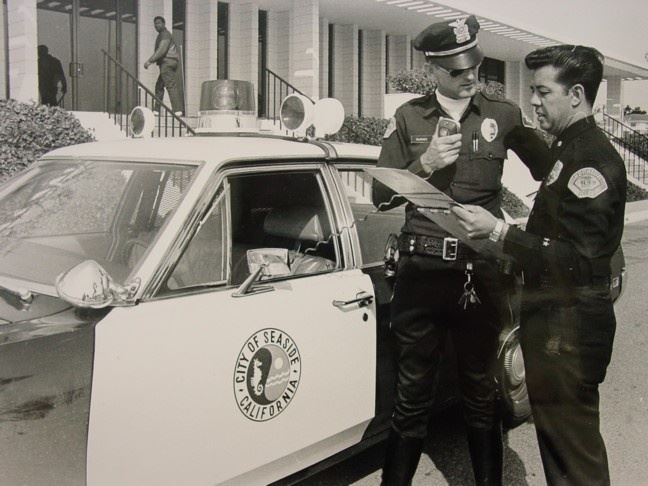 Historical photo of two officers in front of police vehicle