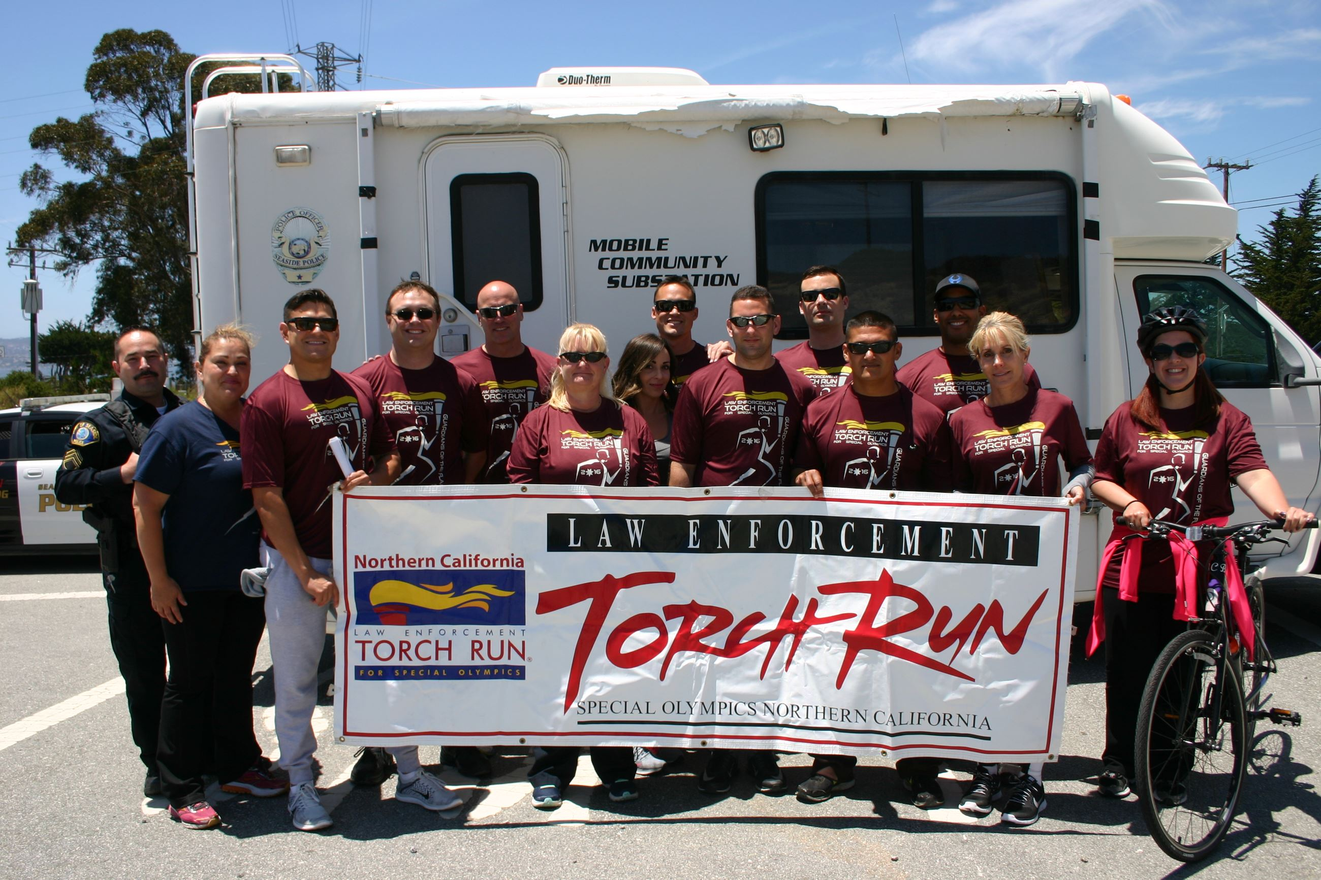 Group photo of Torch Run participants surrounding Torch Run banner