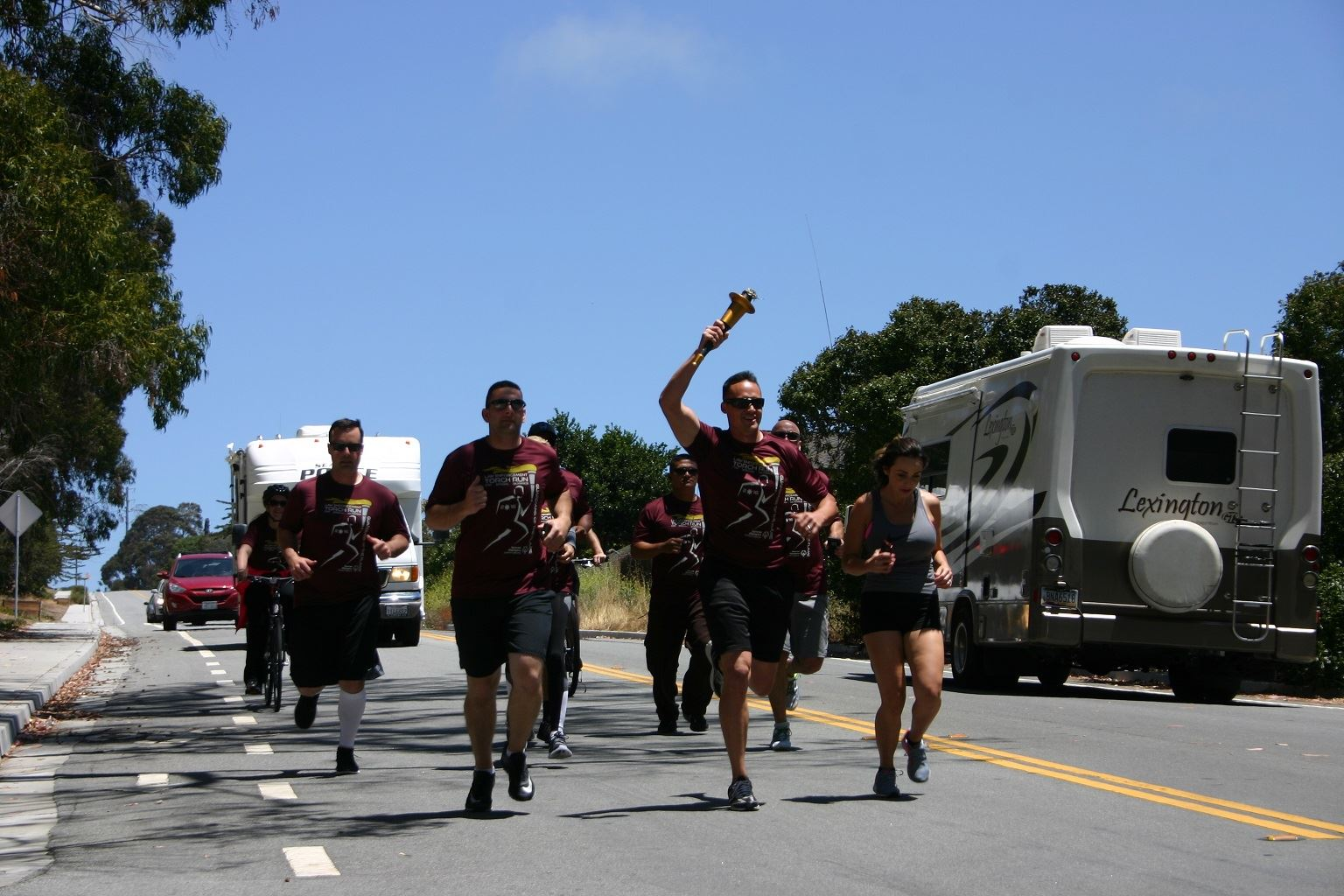 Group of Torch Run participants running on road carrying the torch