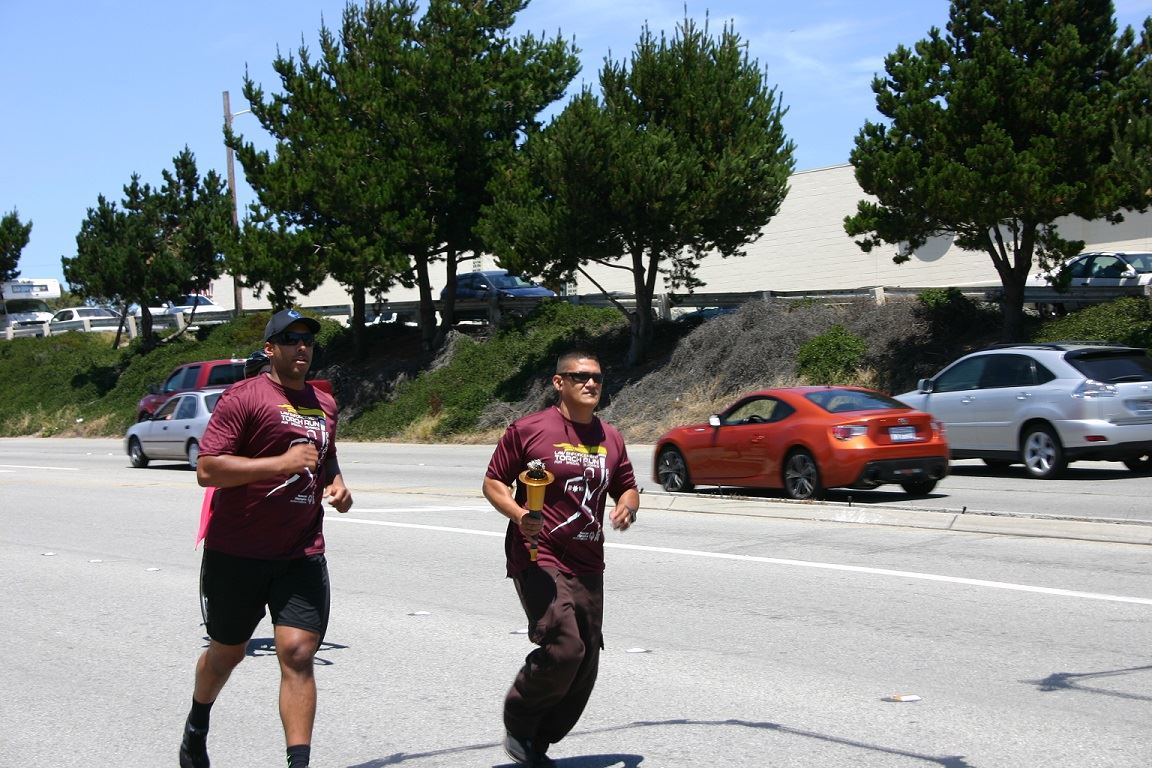Two Torch Run participants running on road carrying torch