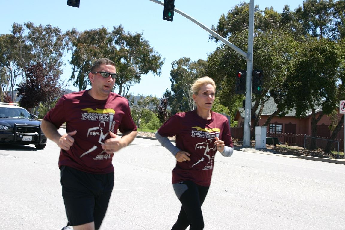 Two Torch Run participants running on Canyon Del Rey in front of PD vehicle