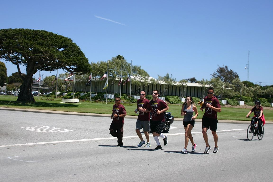 Group of Torch Run participants running on road in front of Seaside City Hall