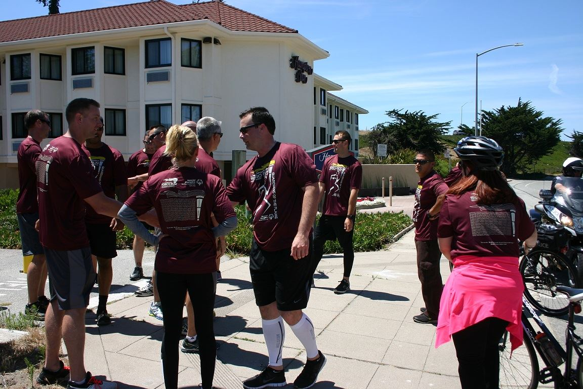 Group of Torch Run participants handing off torch to Monterey PD in front of hotel building