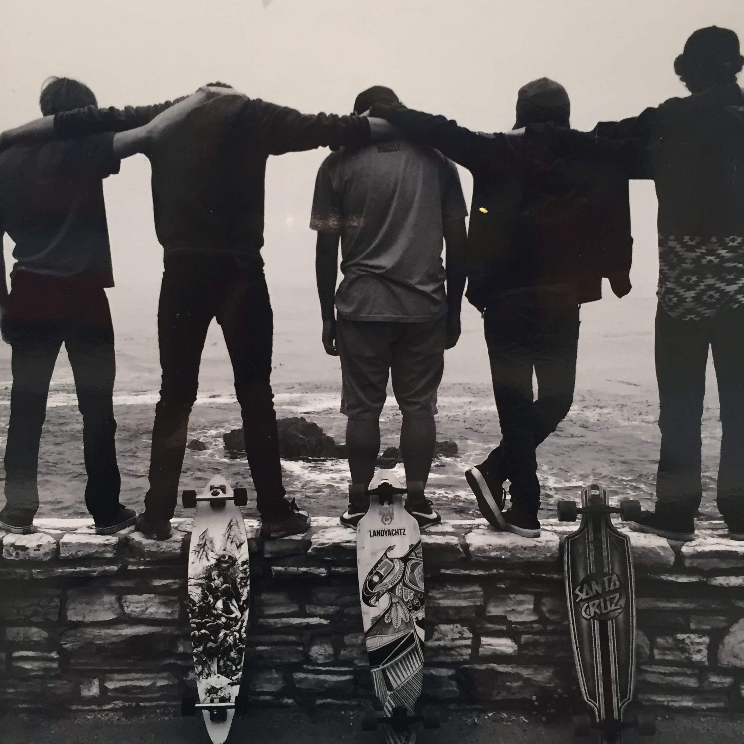 Black and white photo of three people with skateboards standing on brick wall facing the ocean