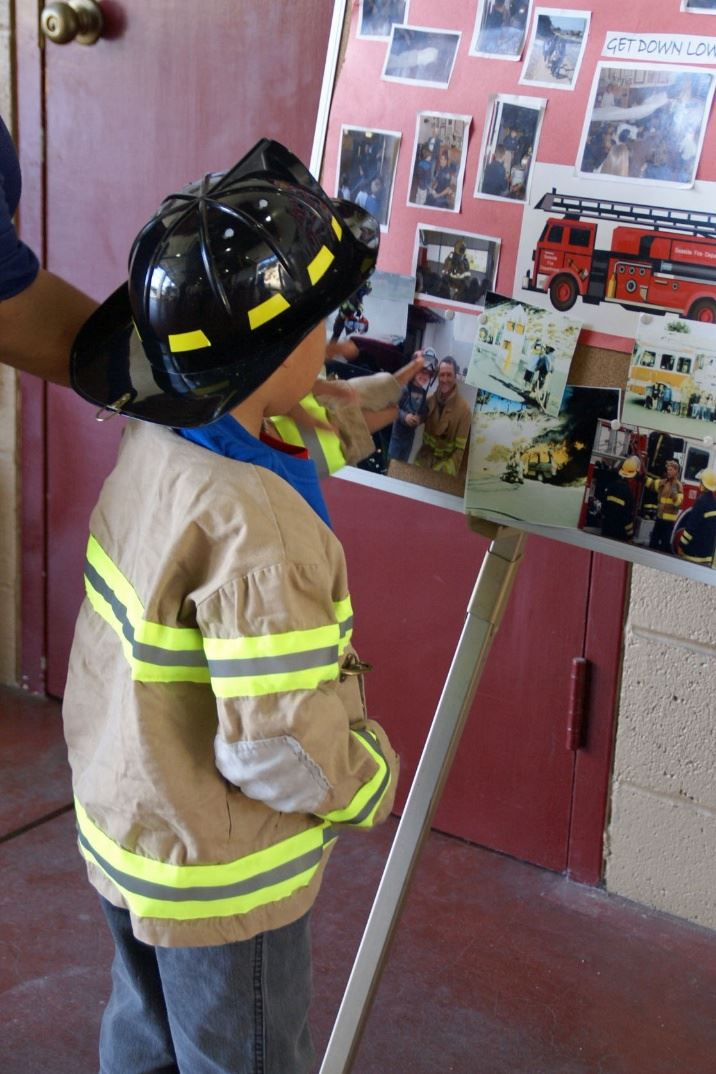 Boy Dressed Up Like a Firefighter looking at a collage